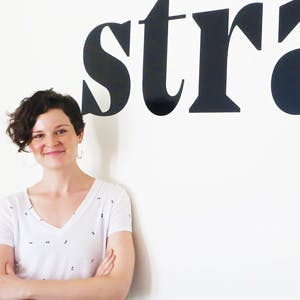 Alli Reed standing in front of the Stratia logo