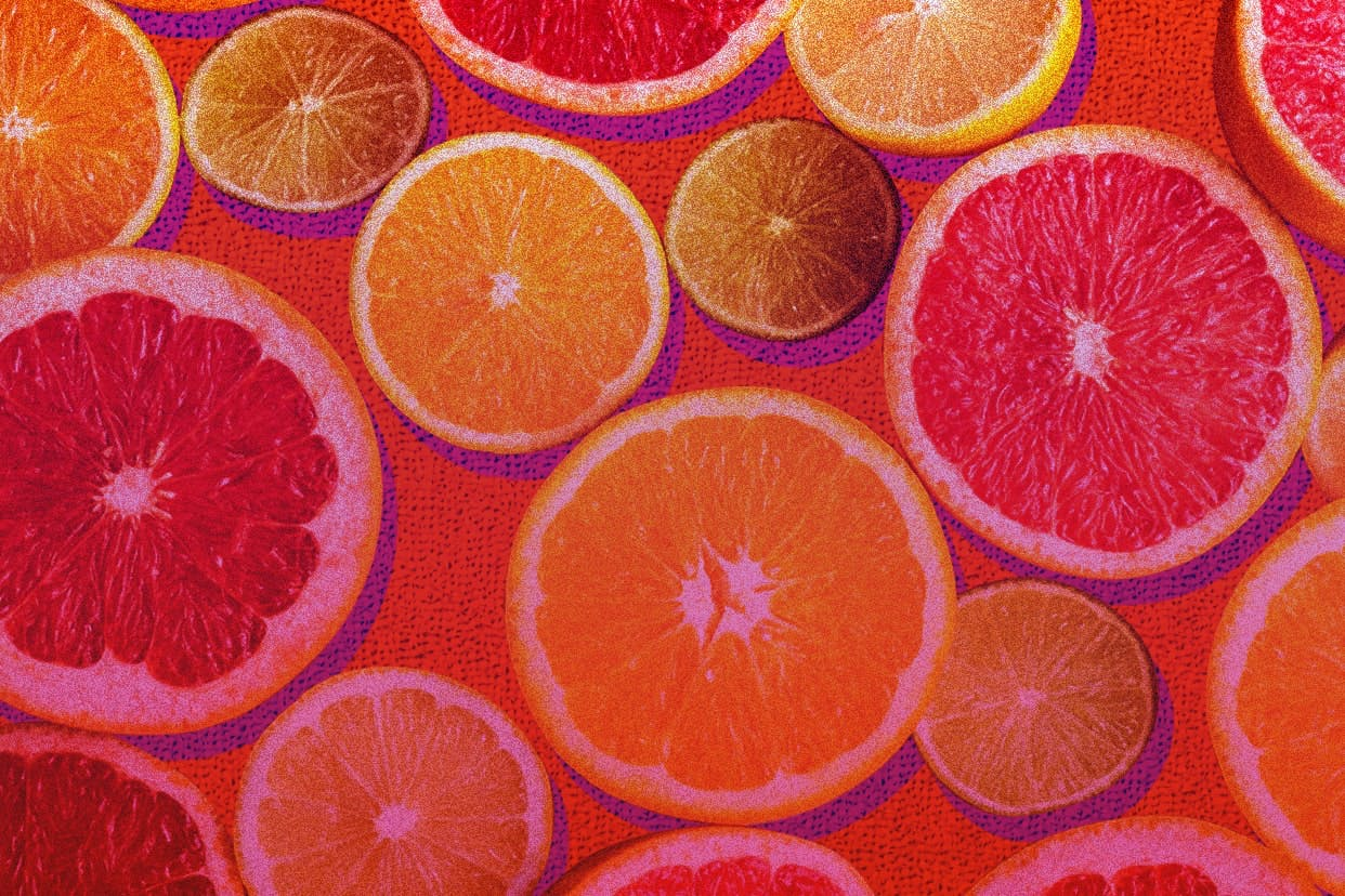 oranges and grapefruit slices on a pink background