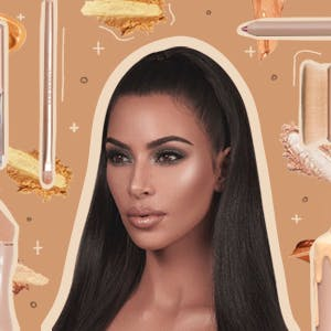 Kim Kardashian West wearing her makeup brand surrounded by various products from her brand KKW Beauty